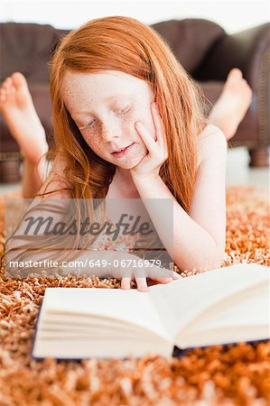 Girl reading on living room floor Stock Photo - Premium Royalty-Free, Image code: 649-06716979