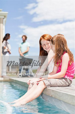 Girls dangling feet in swimming pool Stock Photo - Premium Royalty-Free, Image code: 649-06716986
