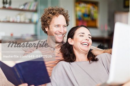 Couple reading together on sofa Stock Photo - Premium Royalty-Free, Image code: 649-06717025