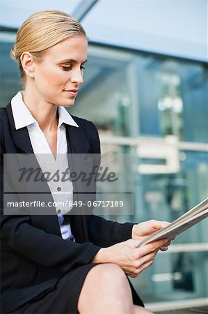 Businesswoman reading newspaper Stock Photo - Premium Royalty-Free, Image code: 649-06717189