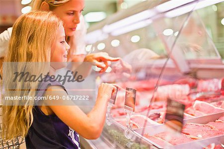 Mother and daughter at butcher counter Stock Photo - Premium Royalty-Free, Image code: 649-06717222