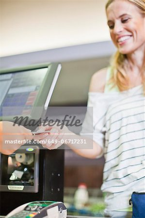 Woman paying with credit card in store Stock Photo - Premium Royalty-Free, Image code: 649-06717231