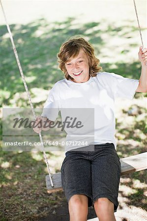 Boy playing on swing in park Stock Photo - Premium Royalty-Free, Image code: 649-06717244