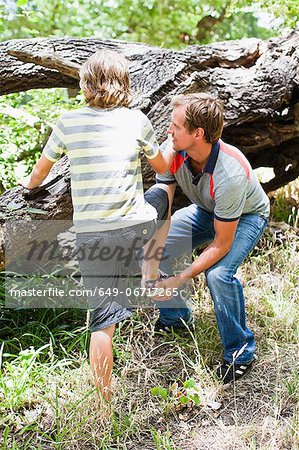 Father helping son over fallen tree Stock Photo - Premium Royalty-Free, Image code: 649-06717265