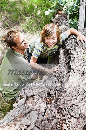 Father helping son over fallen tree Stock Photo - Premium Royalty-Free, Image code: 649-06717266