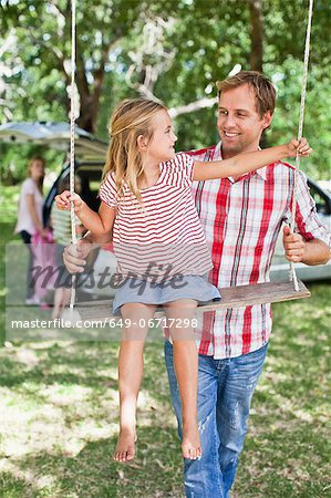 Father pushing daughter on swing Stock Photo - Premium Royalty-Free, Image code: 649-06717298
