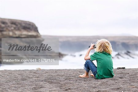 Boy using binoculars on beach Stock Photo - Premium Royalty-Free, Image code: 649-06717326