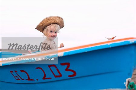 Toddler girl sitting in boat on beach Stock Photo - Premium Royalty-Free, Image code: 649-06717330