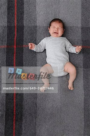 Baby boy crying on bed Stock Photo - Premium Royalty-Free, Image code: 649-06717446