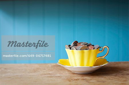 Teacup full of money on desk Stock Photo - Premium Royalty-Free, Image code: 649-06717481