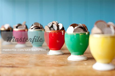 Egg cups full of money on desk Stock Photo - Premium Royalty-Free, Image code: 649-06717484