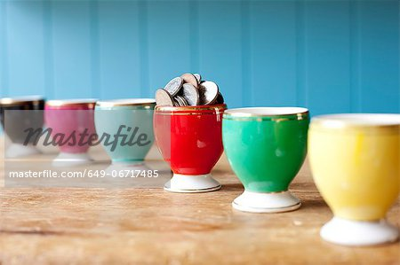 Egg cup full of money on desk Stock Photo - Premium Royalty-Free, Image code: 649-06717485