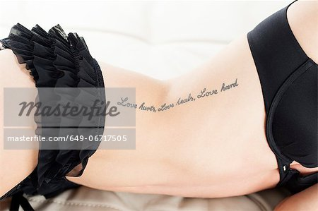 Woman in lingerie with text tattoo Stock Photo - Premium Royalty-Free, Image code: 649-06717505