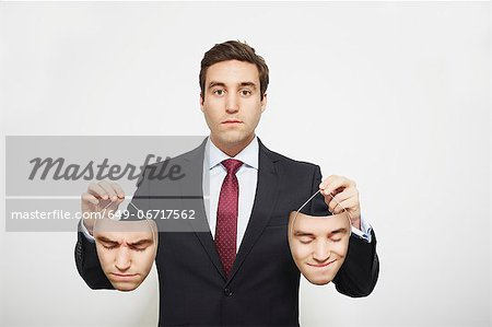 Businessman holding masks Stock Photo - Premium Royalty-Free, Image code: 649-06717562