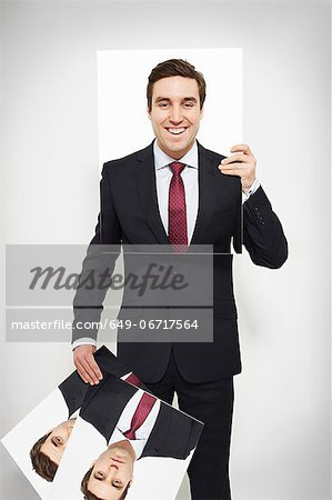 Businessman holding happy picture over his face Stock Photo - Premium Royalty-Free, Image code: 649-06717564