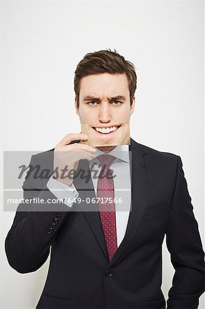 Businessman holding angry picture over his face Stock Photo - Premium Royalty-Free, Image code: 649-06717566