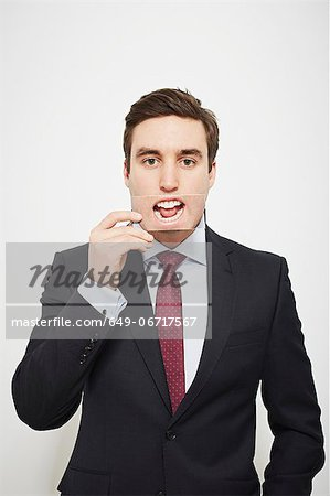 Businessman holding picture over his mouth Stock Photo - Premium Royalty-Free, Image code: 649-06717567