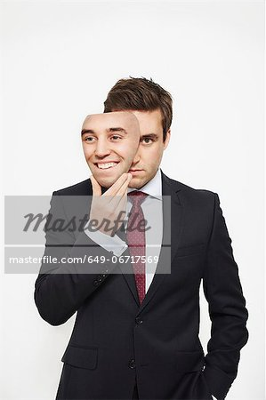 Businessman holding mask over his face Stock Photo - Premium Royalty-Free, Image code: 649-06717569