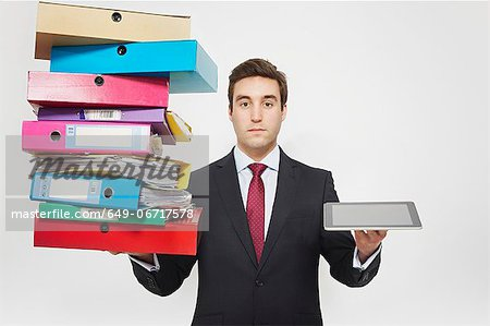Businessman with stacks of folders and tablet computer Stock Photo - Premium Royalty-Free, Image code: 649-06717578