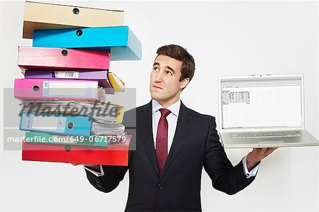 Businessman with stacks of folders and laptop Stock Photo - Premium Royalty-Free, Image code: 649-06717579