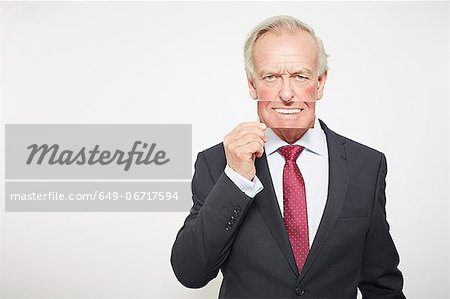 Businessman holding picture over his mouth Stock Photo - Premium Royalty-Free, Image code: 649-06717594