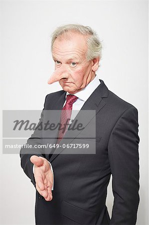 Businessman with long nose offering hand Stock Photo - Premium Royalty-Free, Image code: 649-06717599
