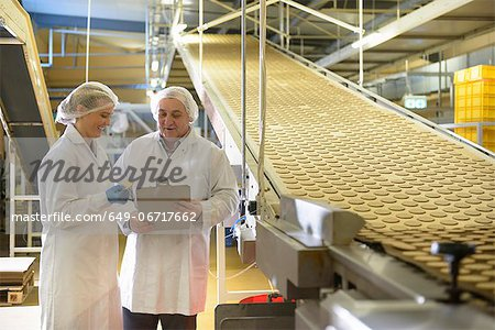 Workers talking in biscuit factory Stock Photo - Premium Royalty-Free, Image code: 649-06717662