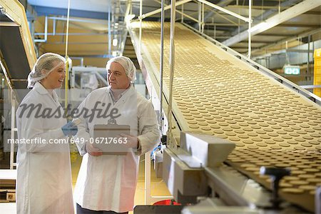 Workers talking in biscuit factory Stock Photo - Premium Royalty-Free, Image code: 649-06717663