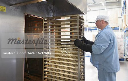 Worker baking biscuits in factory Stock Photo - Premium Royalty-Free, Image code: 649-06717683