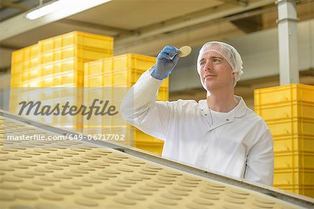 Worker examining biscuit in factory Stock Photo - Premium Royalty-Free, Image code: 649-06717702