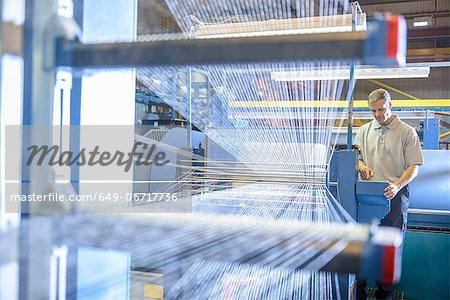 Worker examining loom in textile mill Stock Photo - Premium Royalty-Free, Image code: 649-06717736