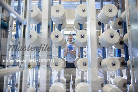 Worker examining thread in textile mill Stock Photo - Premium Royalty-Free, Image code: 649-06717738