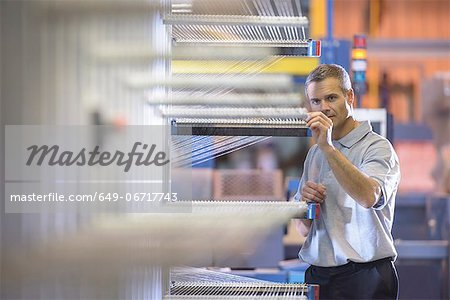 Worker examining loom in textile mill Stock Photo - Premium Royalty-Free, Image code: 649-06717743