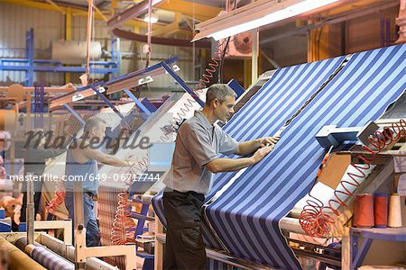 Worker examining loom in textile mill Stock Photo - Premium Royalty-Free, Image code: 649-06717744