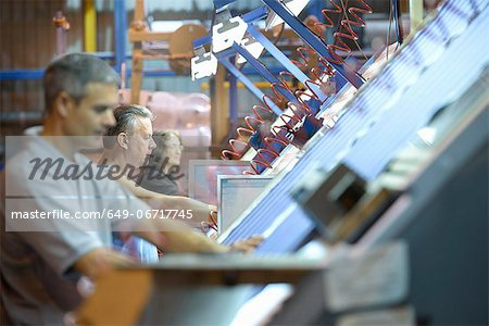 Workers examining loom in textile mill Stock Photo - Premium Royalty-Free, Image code: 649-06717745
