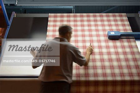 Worker examining fabric in textile mill Stock Photo - Premium Royalty-Free, Image code: 649-06717746