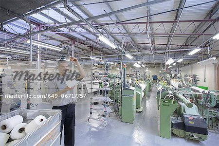 Worker examining thread in textile mill Stock Photo - Premium Royalty-Free, Image code: 649-06717757