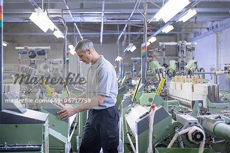 Worker using loom in textile mill Stock Photo - Premium Royalty-Free, Image code: 649-06717759
