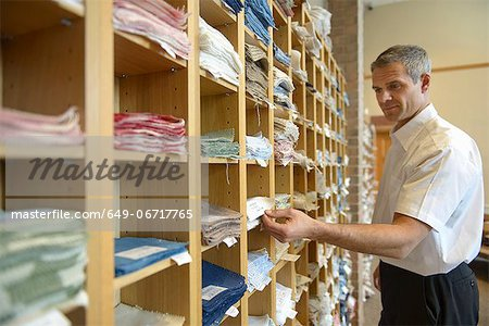 Worker examining fabric in textile mill Stock Photo - Premium Royalty-Free, Image code: 649-06717765