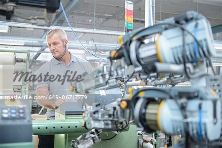 Worker using loom in textile mill Stock Photo - Premium Royalty-Free, Image code: 649-06717779