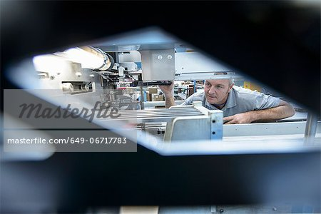 Worker using machinery in textile mill Stock Photo - Premium Royalty-Free, Image code: 649-06717783