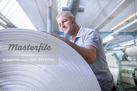 Worker examining fabric in textile mill Stock Photo - Premium Royalty-Free, Image code: 649-06717785