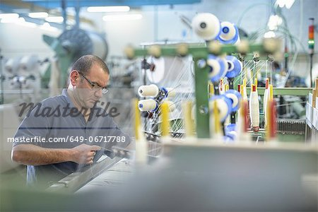 Worker using loom in textile mill Stock Photo - Premium Royalty-Free, Image code: 649-06717788