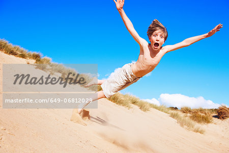 Boy falling on sand dune Stock Photo - Premium Royalty-Free, Image code: 649-06812029