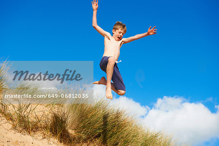 Boy jumping on beach Stock Photo - Premium Royalty-Free, Image code: 649-06812035