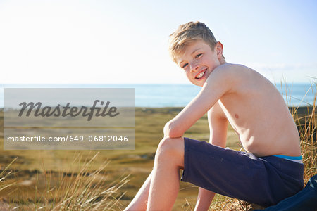 Boy sitting on beach Stock Photo - Premium Royalty-Free, Image code: 649-06812046