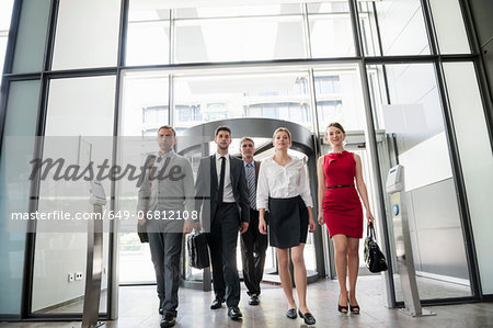 Group of business people walking into glass office building Stock Photo - Premium Royalty-Free, Image code: 649-06812108