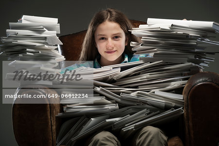 Girl sitting in leather armchair with piles of books, smiling Stock Photo - Premium Royalty-Free, Image code: 649-06812234