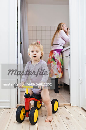 Toddler girl playing on tricycle, mother in background Stock Photo - Premium Royalty-Free, Image code: 649-06812252