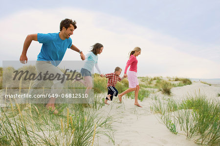 Family holding hands and running at the beach